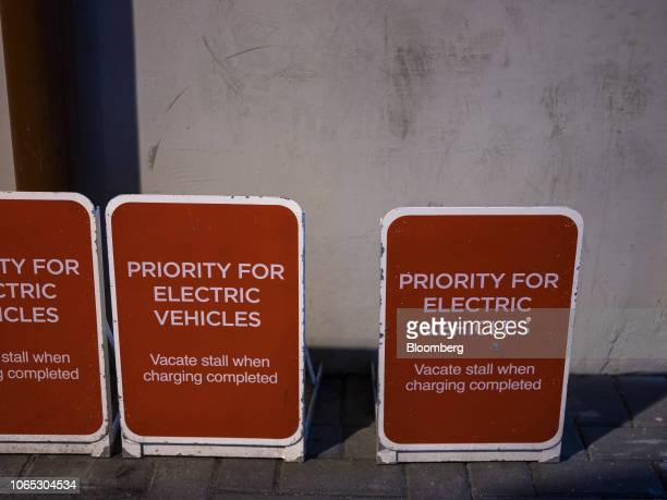 Signs reading Priority For Electric Vehicles stand inside a parking lot in Hong Kong China on Friday Nov 23 2018 Hong Kong's administration scrapped...