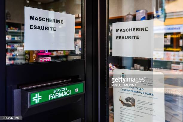 Signs reading Protective Repiratory Masks Sold Out are put up on a pharmacy's window in Codogno southeast of Milan on February 22 2020 An Italian man...