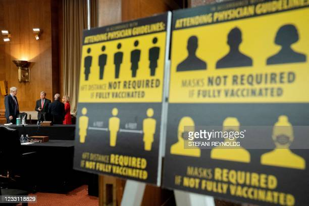 Signs requiring masks if not vaccinated against Covid-19 are displayed as Francis Collins, director of the U.S. National Institutes of Health , from...