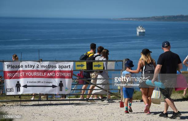 Signs stating to stay 2 metres apart at Durdle Door beach on May 25, 2020 in West Lulworth, United Kingdom. The British government has started easing...