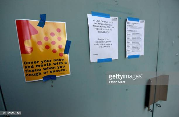 Signs taped to a locked door at Centennial High School show instructions for sneezing and coughing and that the school is closed as well as locations...