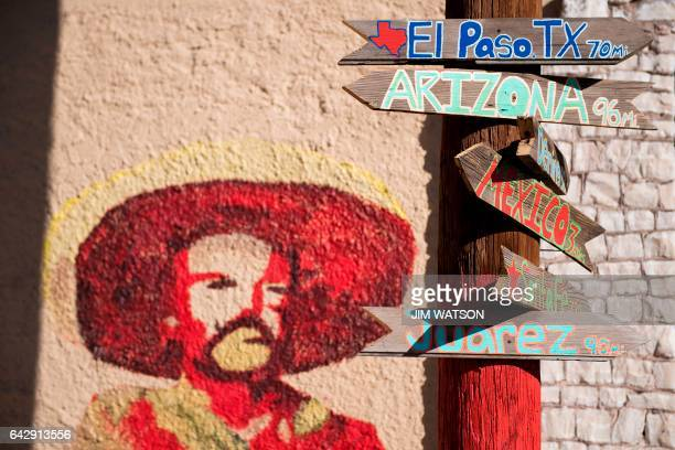 Signs telling the miles to different cities stands next to a mural of Mexican revolutionary leader Pancho Villa in Columbus New Mexico on February 19...