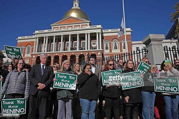 Signs thanking Boston mayor Thomas M Menino are displayed as the funeral procession passes by the State House