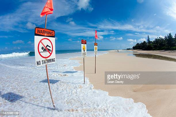 signs, warning of dangerous surf - hawaii flag stock pictures, royalty-free photos & images