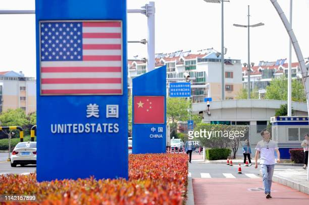 Signs with the US flag and Chinese flag are seen at the Qingdao free trade port area in Qingdao in China's eastern Shandong province on May 8, 2019....