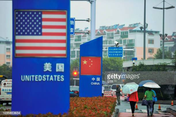 Signs with the US flag and Chinese flag are seen outside a store selling foreign goods in Qingdao in China's eastern Shandong province on September...