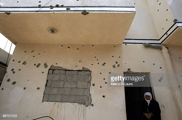 Siham Kishta 45yearsold stands in front of her bullet hole scarred house on September 19 2005 in Rafah refugee camp Gaza Strip Siham Kishta and her...