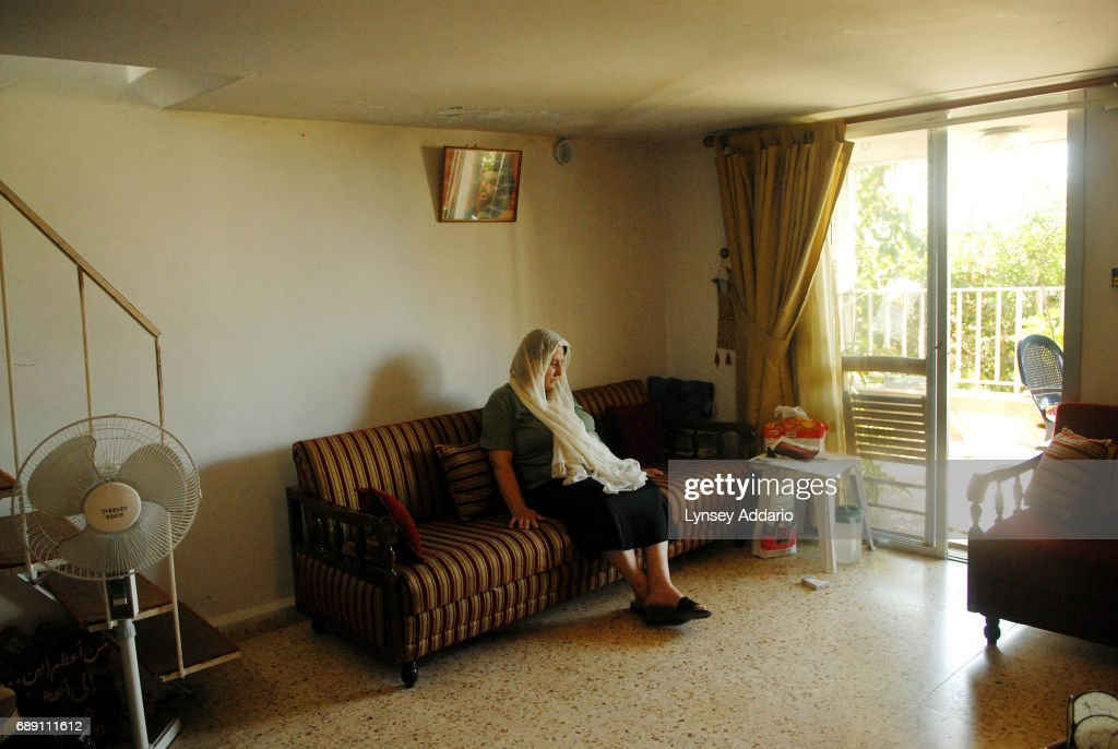 Siham Kuntar, the Step-mother of political prisoner, Samir Kuntar, sits at home beneath a picture of Hezbollah leader, Hassan Nasrullah, in the village of Abey, in the mountains outside of Beirut, Lebanon, September 17, 2006. Kuntar has been held in an Israeli jail for over twenty years, since being caught in a foiled attempt to take political prisoners from a home in Naharriya, Israel. He is also accused of killing a father and daughter when the operation went awray.