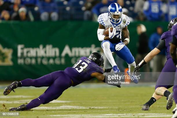 Sihiem King of the Kentucky Wildcats jumps over Warren Long of the Northwestern Wildcats during the Music City Bowl at Nissan Stadium on December 29...