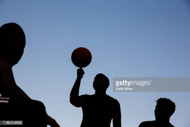 Sihouette of sportsmen on blue sky as one spins a ball on his thumb
