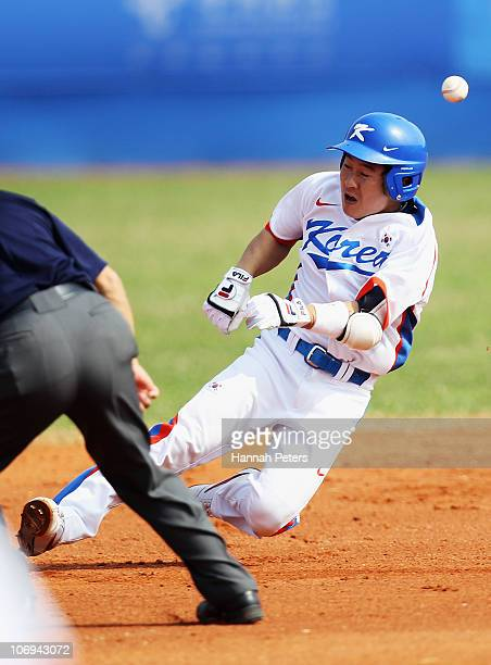 Sihyun Son of Korea dives into second base during the baseball match between Korea and China during day six of the 16th Asian Games Guangzhou 2010 at...