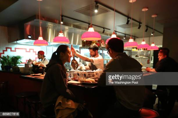 Sijie Tian and Irene Yu eat dinner at Tiger Fork while Chef Irvin Van Oordt prepares a bubble waffle behind the counter in Washington DC on March 11...