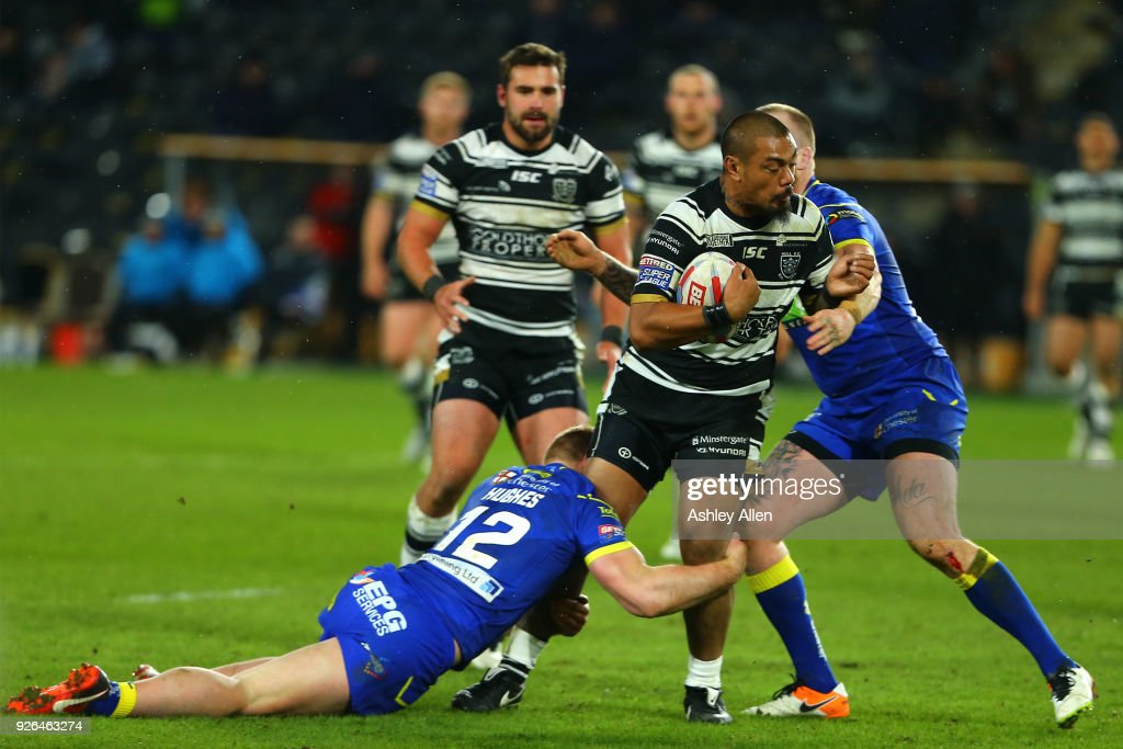 Sika Manu of Hull FC is tackled by Jack Hughes and Kevin Brown of Warrington Wolves during the BetFred Super League match between Hull FC and Warrington Wolves at KCOM Stadium on March 2, 2018 in Hull, England.