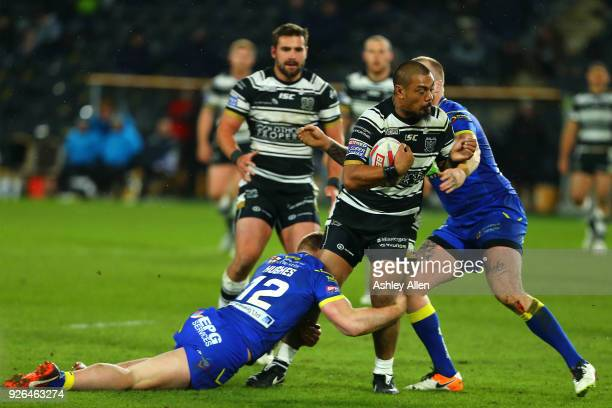 Sika Manu of Hull FC is tackled by Jack Hughes and Kevin Brown of Warrington Wolves during the BetFred Super League match between Hull FC and...