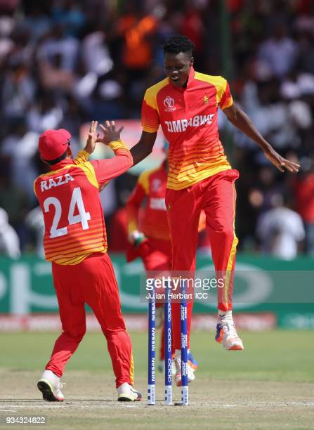 Sikander Razza and Blessing Muzarabani of Zimbabwe celebrate the wicket of Chris Gayle of The West Indies during The Cricket World Cup Qualifier...