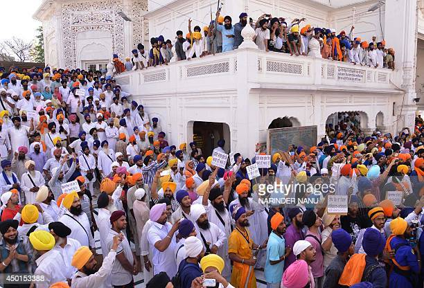 Sikh activists hold posters as they protest during commemorations for the 30th anniversary of Operation Blue Star at the Golden Temple in Amritsar on...