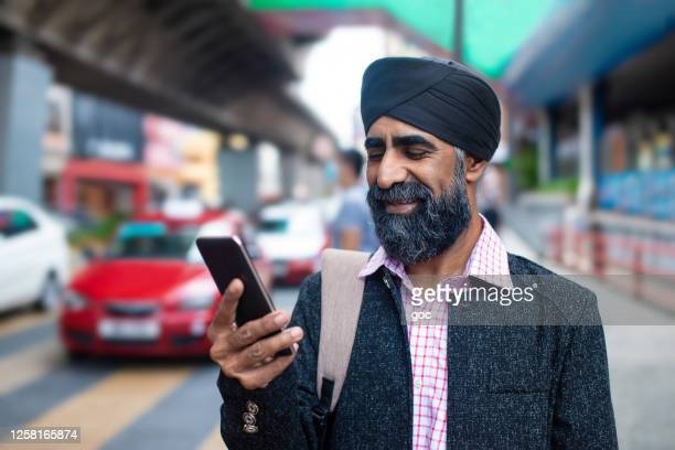 a sikh businessman with turban using smart phone for e-healing on street - south asia stock pictures, royalty-free photos & images