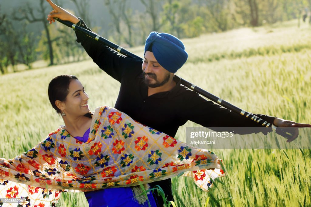 Sikh couple dancing in a Wheat field