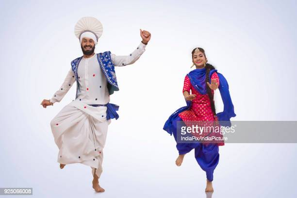 sikh couple doing bhangra dance - lohri festival stock pictures, royalty-free photos & images