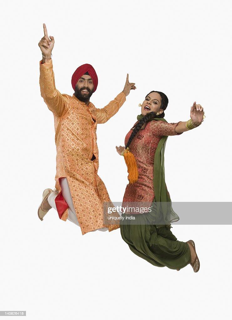 Sikh couple doing Bhangra the folk dance of Punjab in India