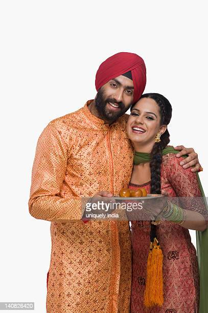 sikh couple holding a plate of gulab jamuns the traditional indian sweet - traditional clothing stock pictures, royalty-free photos & images