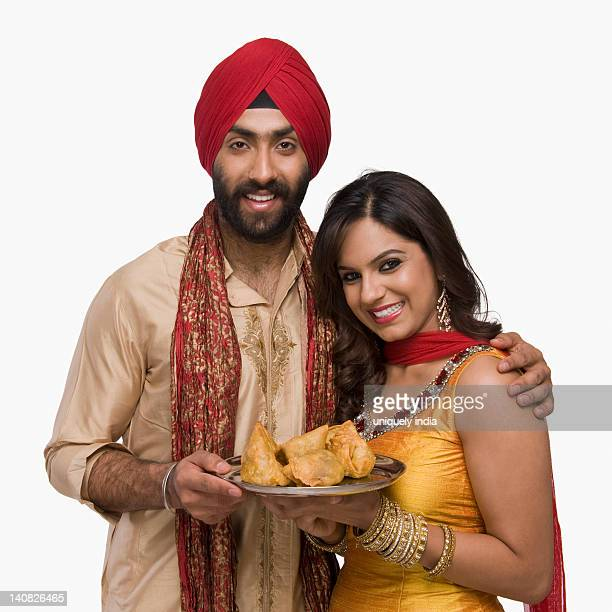 sikh couple holding a plate of samosa the traditional indian snack - traditional clothing stock pictures, royalty-free photos & images