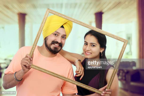 Sikh couple holding an empty picture frame