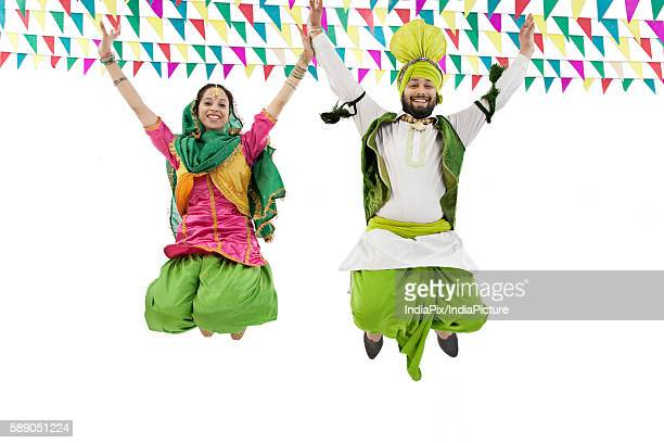 Sikh couple jumping in the air