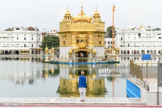 A Sikh devotee pays respect at the deserted Golden Temple during the first day of a 21day governmentimposed nationwide lockdown as a preventive...