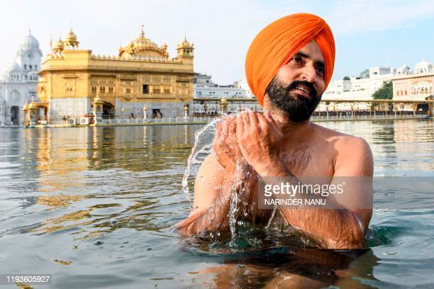 A Sikh devotee takes a dip in the holy sarovar on the occasion of Sikh 'Maghi Mela' festival following the Lohri or harvest festival at the Golden...