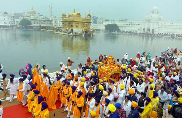 Sikh devotees carry Sri Guru Granth Sahib Ji the holy book of the Sikh religion in a special golden palanquin at the Golden Temple during a religious.