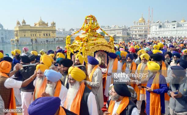 Sikh devotees carry the holy book of the Sikh religion in a special golden palanquin at the Golden Temple during a religious procession on the eve of...