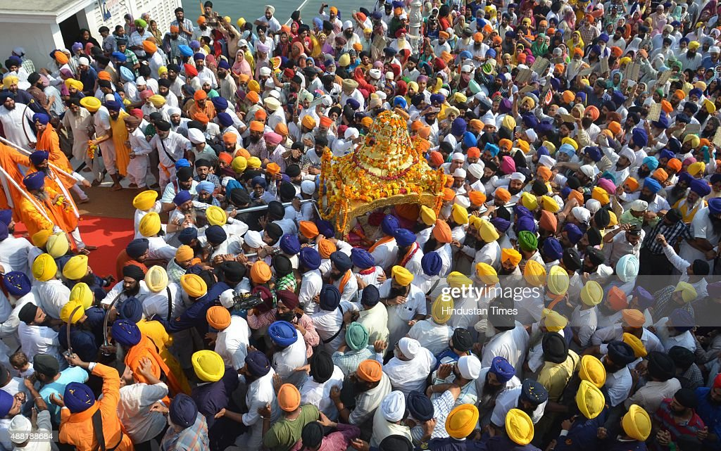 Sikh devotees carry The Palki Sahib during a procession to mark the 411th anniversary of the installation of the Guru Granth Sahib at Golden Temple...