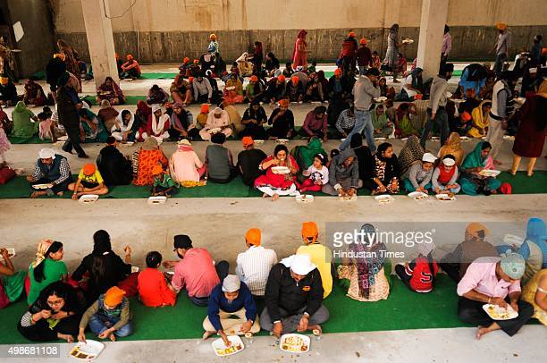 Sikh devotees eat langar on the birth anniversary of Guru Nanak Dev at Gurudwara, on November 25, 2015 in Noida, India. Guru Nanak's Prakash Utsav...
