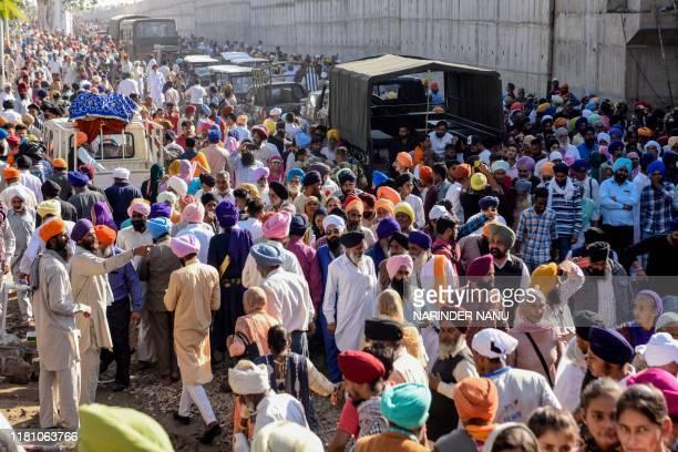 Sikh devotees gather to offer prayers towards the Shrine of Baba Guru Nanak Dev at Gurdwara Darbar Sahib during the inauguration ceremony in...