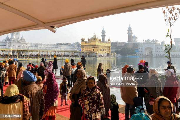 Sikh devotees gather to pay respect on the occasion of Sikh 'Maghi Mela' festival, following the Lohri or harvest festival, at the Golden Temple in...