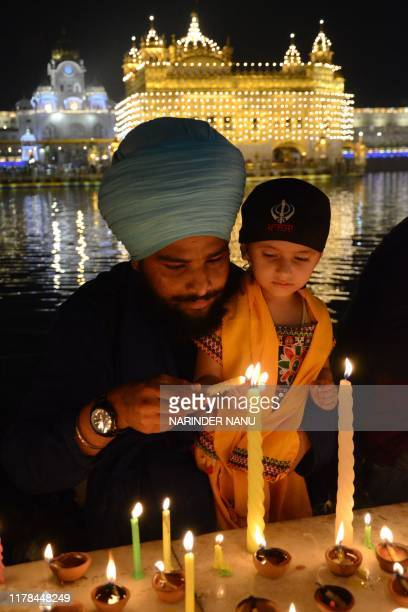 Sikh devotees light candles during Bandi Chhor Divas or Diwali celebrations at the Golden Temple in Amritsar on October 27 2019 Sikhs celebrate Bandi...