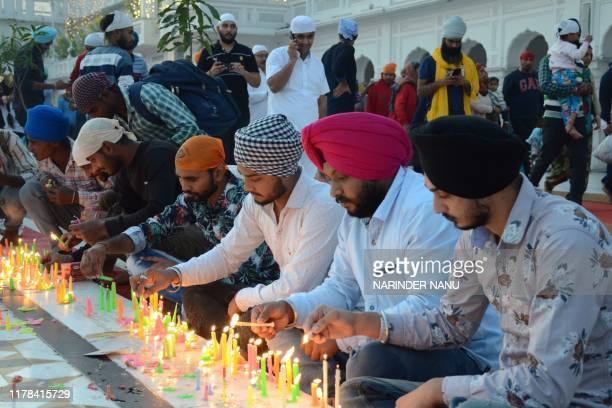 Sikh devotees light candles during Bandi Chhor Divas which coincides with the day of Diwali at the Golden Temple in Amritsar on October 27 2019 Sikhs...