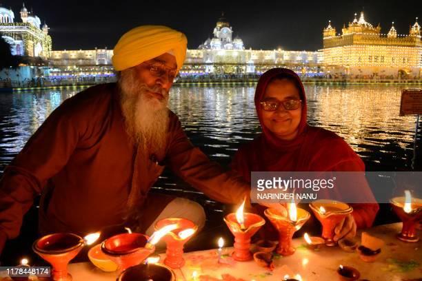 Sikh devotees light oil lamps during Bandi Chhor Divas or Diwali celebrations at the Golden Temple in Amritsar on October 27 2019 Sikhs celebrate...