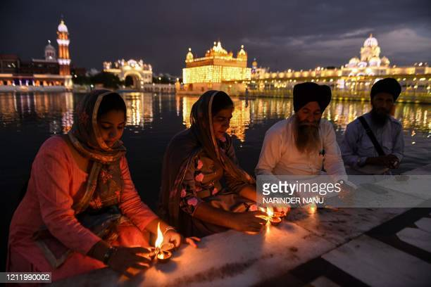 TOPSHOT Sikh devotees light oil lamps on the occasion of the 541th birth anniversary of Guru Amar Das at the Golden Temple during a governmentimposed...