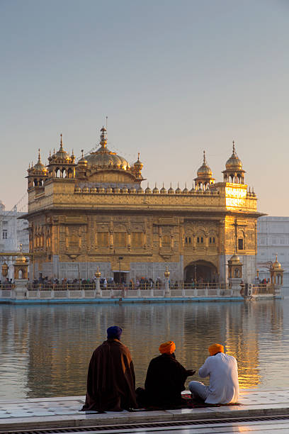 Sikh devotees looking at Golden Temple at dawn