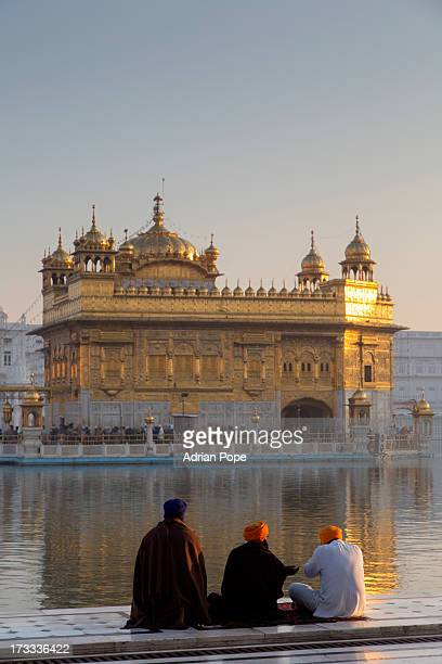 sikh devotees looking at golden temple at dawn - golden temple india stock photos and pictures