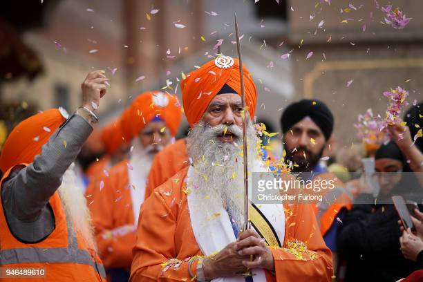 Sikh devotees of the Guru Nanak Sikh Gurdwara community throw flower petals as sword bearers parade through the streets of Walsall to celebrate...