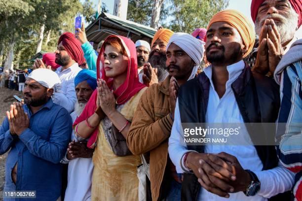 Sikh devotees offer prayers as they look towards the Shrine of Baba Guru Nanak Dev at Gurdwara Darbar Sahib during the inauguration ceremony in...