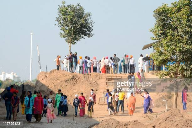 Sikh devotees offers prayers as they look towards the Gurdwara Kartarpur Sahib which is situated in Pakistan after Joint Secretary of Indian Home...