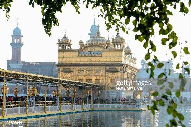 Sikh devotees pay respect on the occasion of Sikh 'Maghi Mela' festival following the Lohri or harvest festival at the Golden Temple in Amritsar on...
