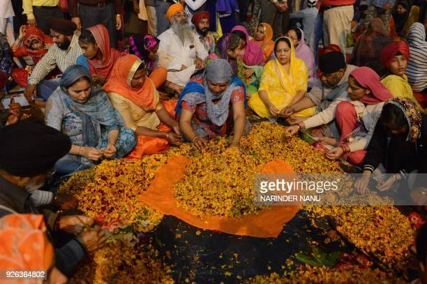 Sikh devotees pluck flower petals on the Palki Sahib which carries the Guru Garnth Sahib to mark 'Hola Mohalla' in a procession from the Golden...