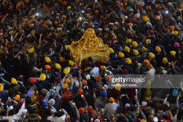 Sikh devotees spray perfume and shower flower petals on the Palki Sahib which carries the Guru Garnth Sahib to mark 'Hola Mohalla' during a...