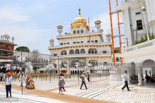 Sikh devotees walk past the Akal Takhat building complex ahead of the 36th Operation Blue Star Anniversary at the Golden Temple in Amritsar on June...