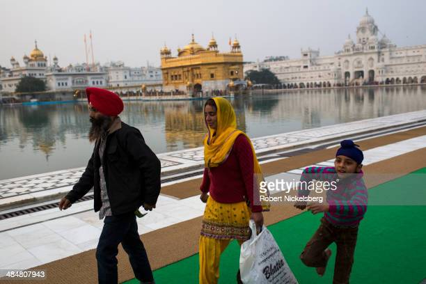 Sikh family walks along a reservoir February 22 2014 at the Golden Temple in Amritsar India The Golden Temple is the sacred shrine for the followers...